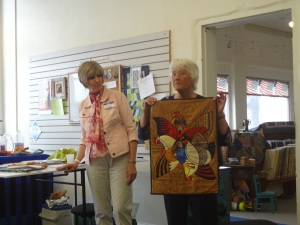 Janney holds a beautiful quilt for us to see!  (Cindy on the left)