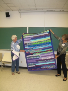 Janney, left, and Cindy, right hold up Janney's jelly roll quilt.  Yahoo!!!!