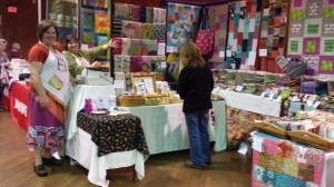 Rhonda, wearing a green top and a big smile is in the Sew Fresh Fabrics booth at the Quilters Gathering Quilt Show in Manchester, NH in 2013. Such a vivacious lady! Sew Fresh Fabrics had a booth at the 2013 Maine Quilt Show in Augusta.