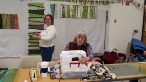 Jane Hann Morey, Liaison to Pine Tree Quilt Guild, and Membership Person to MMQG, left and Karen B., outgoing Co-Sec., working on wedge table runners