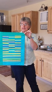 Jen Johnson displays a mod quilt made with 5 colors only.